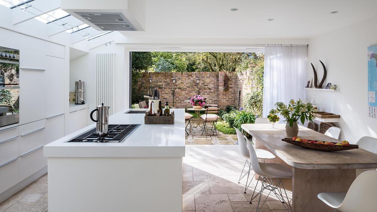 Белый кухонный остров в светлой кухне. Солнце падающее из верхних окон играет на гладкой поверхности кухонной столешницы.
