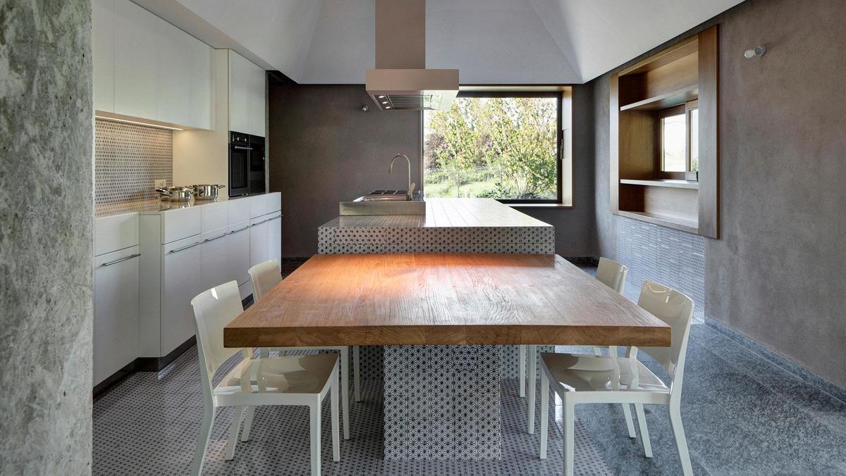 Брутально большой кухонный остров с обеденным столом на кухне интерьером намекающей на кухню общепита с окошком для выдачи блюд.