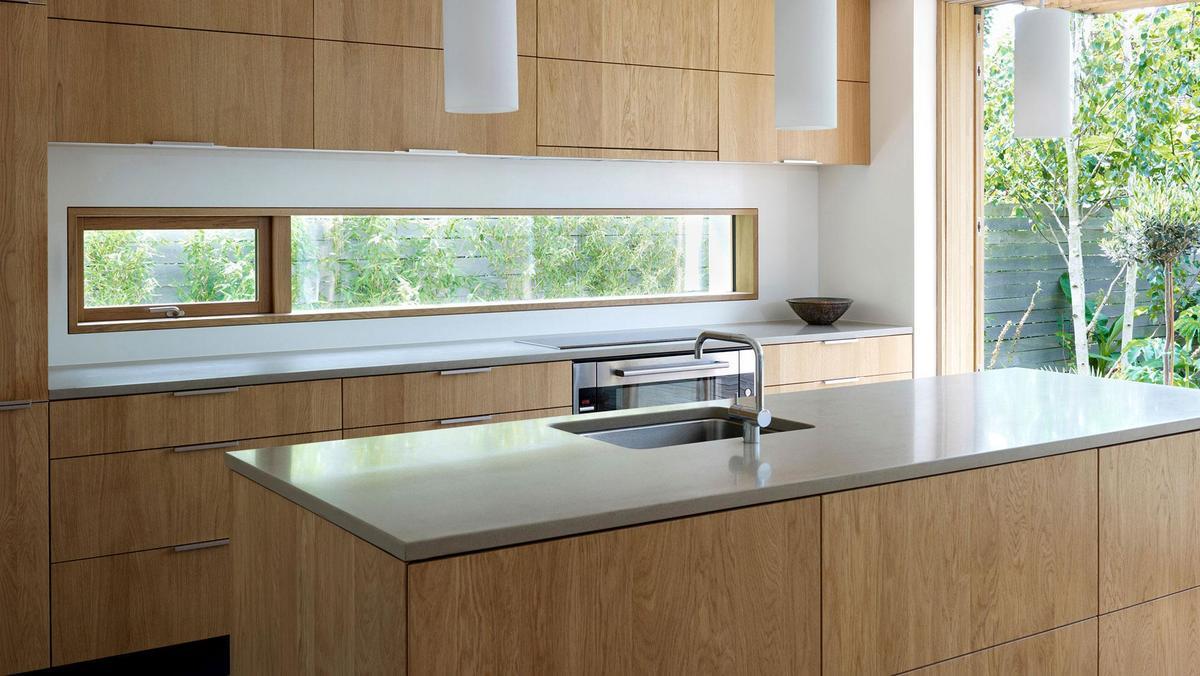 Деревянные фасады и кухонная столешница из композита - просто и элегантно.