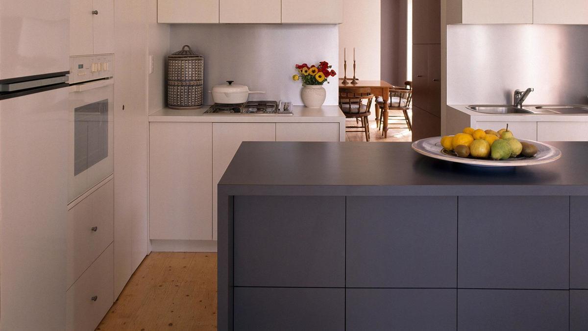 Кухонный остров контрастного серого цвета служит дополнительной поверхностью на кухне.