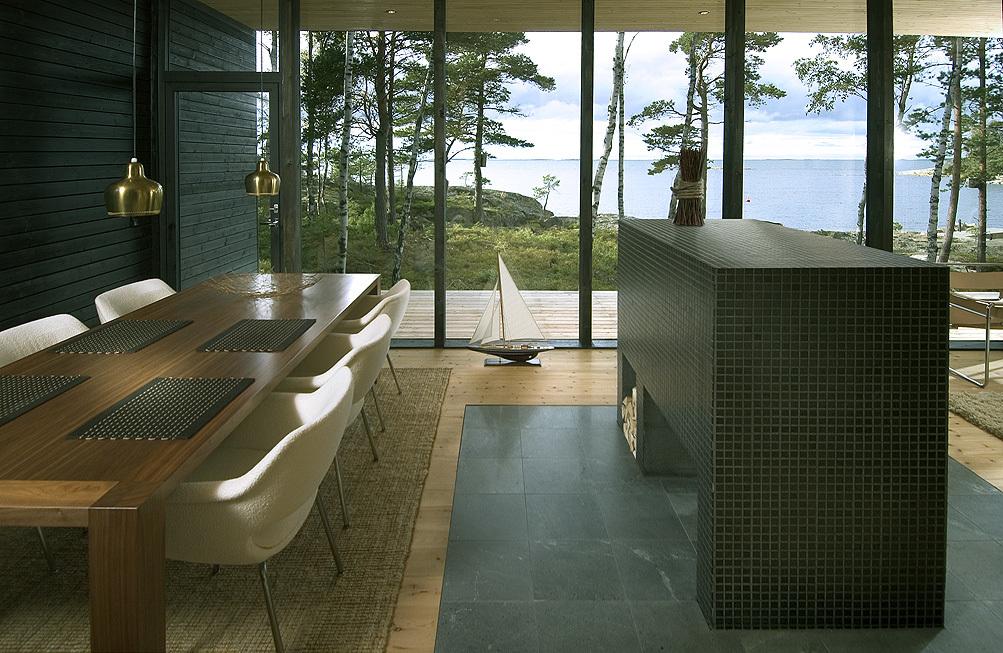Полностью остекленная стена стирает барьер между внутренним и внешним пространством дома впуская окружающую природу в дом и открывая вид на залив.