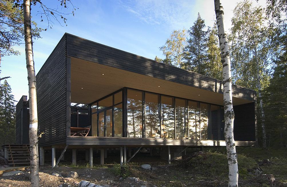 Терраса экранирована деревянной стеной, что защищает от ветра и придает пространству террасы приватности.