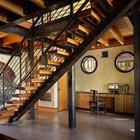 Ажурная конструкция лестницы на второй этаж не закрывает и не разделяет визуально жилое пространство первого этажа дома.