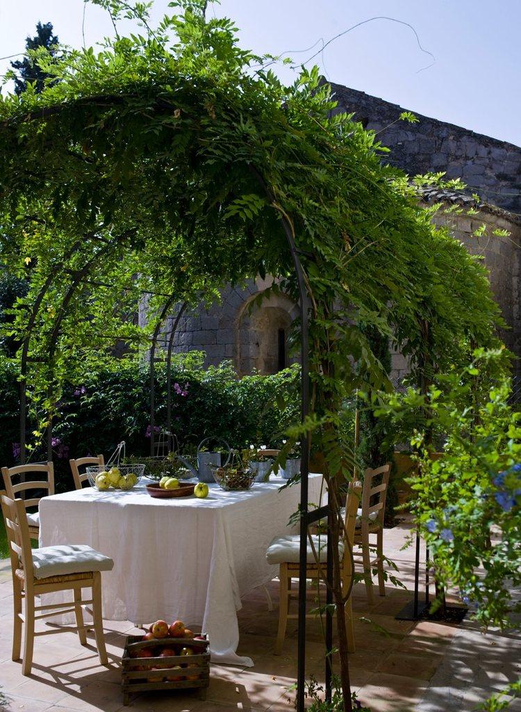 Обеденный стол под аркой с вьющимися растениями