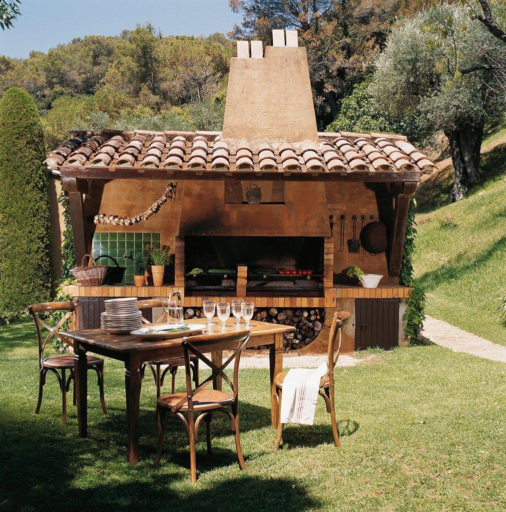 Обеденный стол в саду у полноценной кухни-барбекю выглядит очень логично.