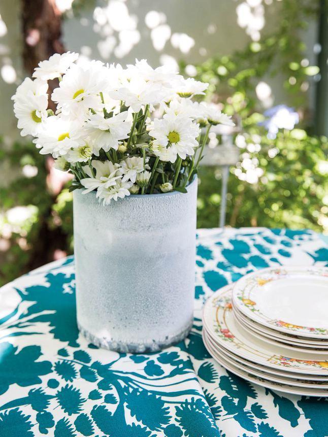 Белая ваза с цветами освежает дизайн столовой на террасе и радует глаз.