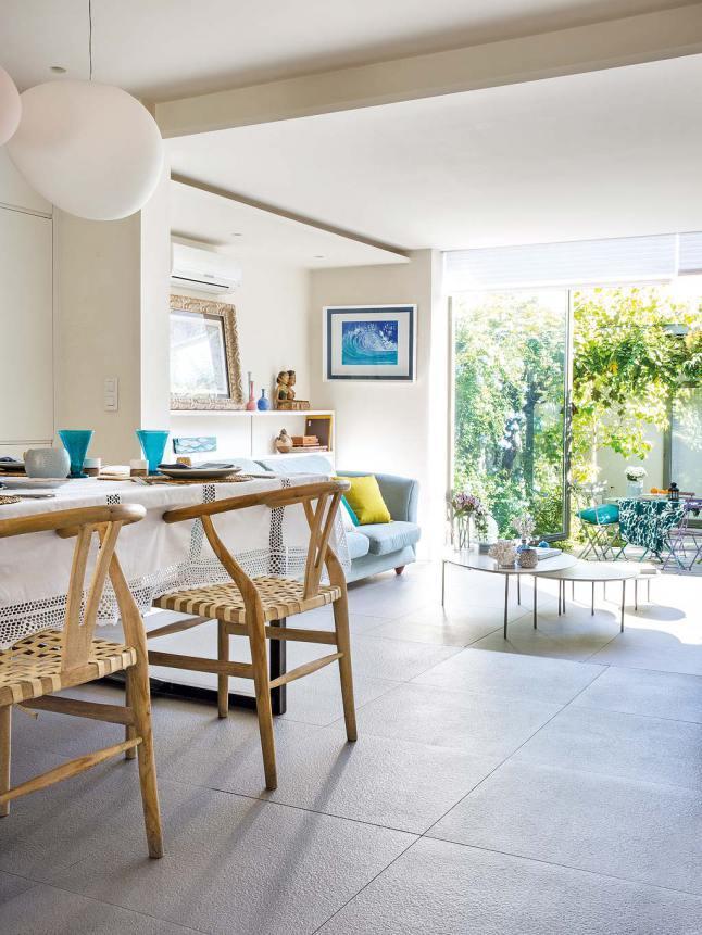 Однородный серый керамический пол подчеркивает преемственность напольного покрытия в столовой, гостиной и на террасе.