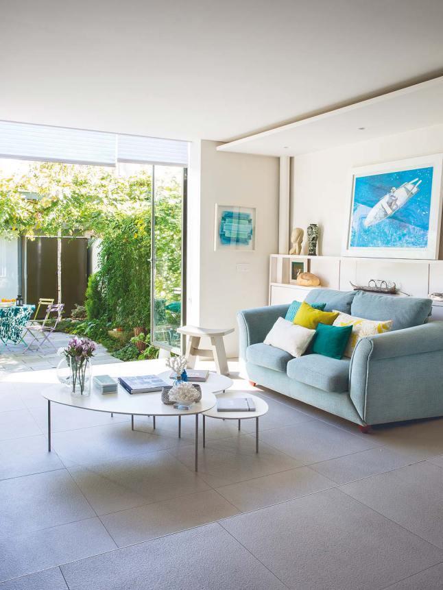 При открытых дверях гостиная становится единым целым с террасой. Зеленые и желтые подушки подчеркивают это единство.