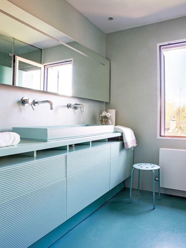 В ванной зеркало и тумбочка под умывальником проходят вдоль всей стены. Цвет тумбочки повторяет цвет пола.