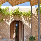 Тенистая терраса рядом с домом. Дверь закрывается интересными деревянными ставнями.