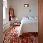 В спальне простые оштукатуренные и побеленные стены, бетонные полы и тщательно подобранный ковер. (архитектура,дизайн,экстерьер,мебель,интерьер,дизайн интерьера,средиземноморский,спальня,дизайн спальни,интерьер спальни)