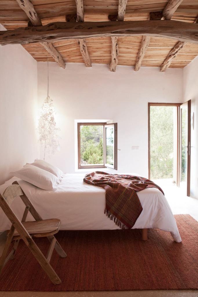 Одна из спален. Причудливые потолки со старыми деревянными балками дизайнер оставил практически в первозданном виде.