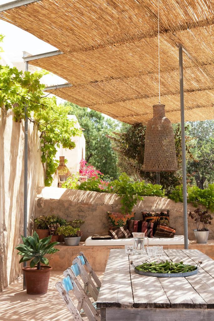 Тенистая терраса с виноградом и соломенной крышей.