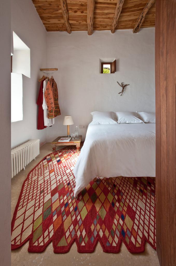 В спальне простые оштукатуренные и побеленные стены, бетонные полы и тщательно подобранный ковер.