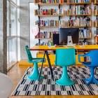 Домашний офис в ярких тонах с большим столом в центре и открытыми стеллажами для книг.