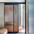 Стеклянные сдвижные двери в спальню с деревянной решеткой повторяющей рисунок бетонной решетки от солнца.