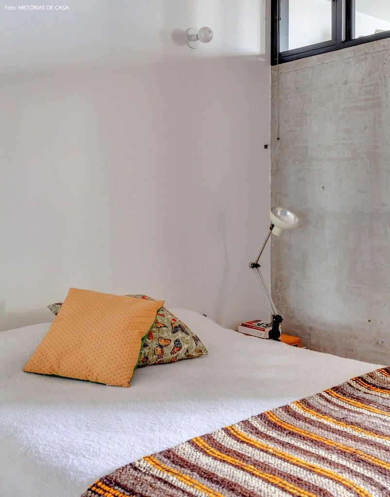 Бетонная стена в спальне и высокие окна.