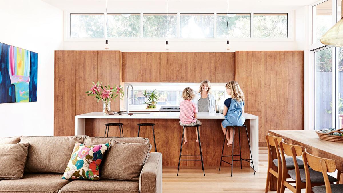 Пристроенная кухня с кухонным островом и окнами под крышей.