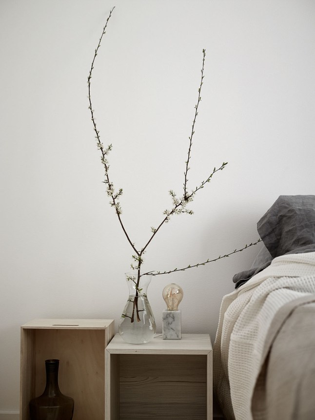 Прикроватные тумбочки в спальне из деревянных ящиков.