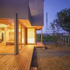 Вечером через большие окна освещаются террасы вокруг дома (фасад,минимализм,архитектура,дизайн,интерьер,экстерьер)