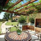 Тенистая терраса под перголой заплетенной виноградом располагает к размеренному проведению времени на свежем воздухе у очага. Эта терраса служит и кухней и столовой.