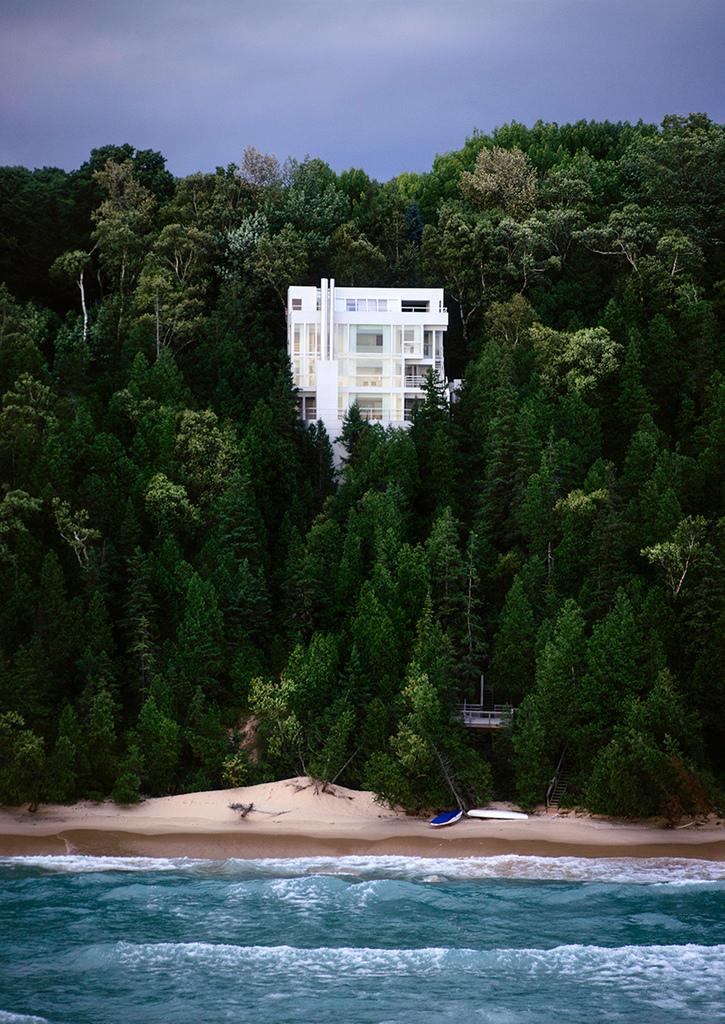 Белый силуэт дома возвышается над зеленым лесистым склоном на берегу озера Мичиган.