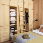 Спальня со шкафом до потолка. Лестница помогает добраться до верхних полок.