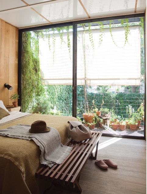 Спальня с остекленной стеной, часто которой сдвигается.