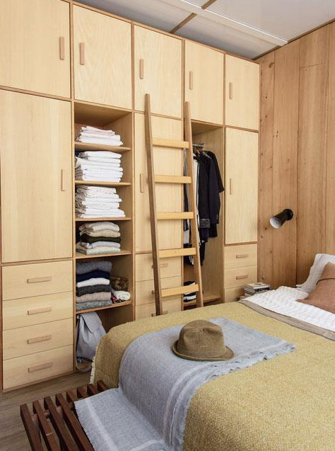 Спальня со шкафом до потолка. Лестница помогает добраться до верхних полок