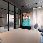 Открытая проводка на бетонном потолке, стеклянная перегородка, картина стоящая на металлической тумбочке, прикроватные светильники на цепях - это и есть спальня в стиле лофт во всей красе.