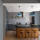 Столешница выполнена из искусственного камня, а кухонные фасады из черненой матовой стали.