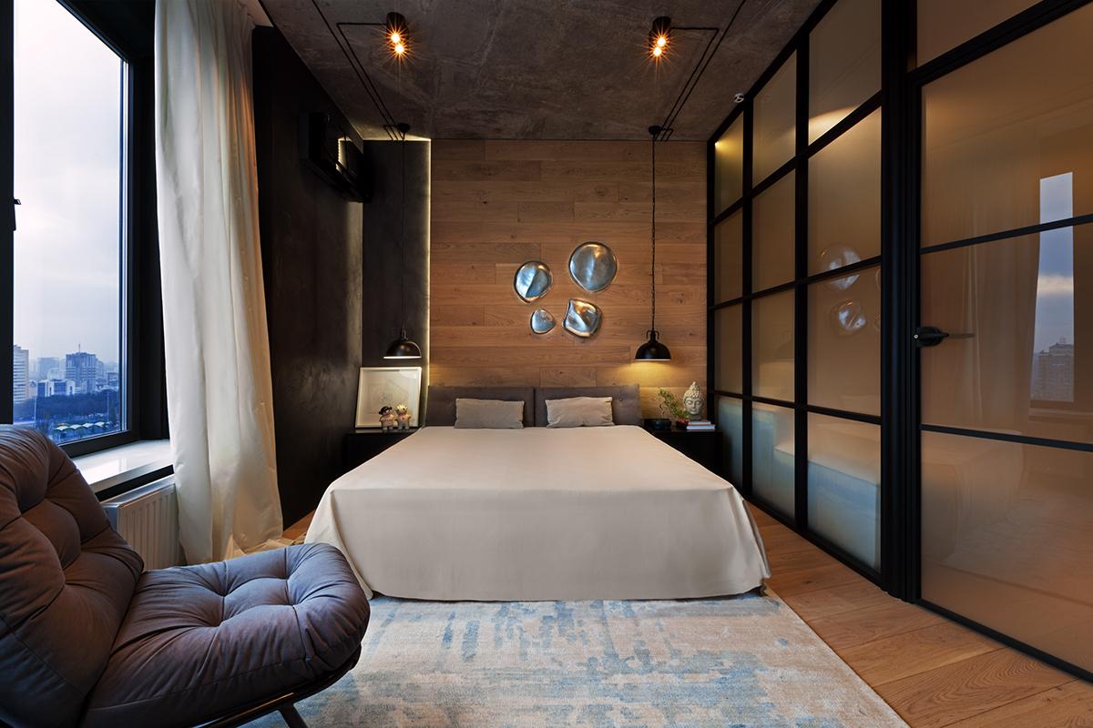 Мягкое кресло призвано смягчить аскетичный интерьер спальни.