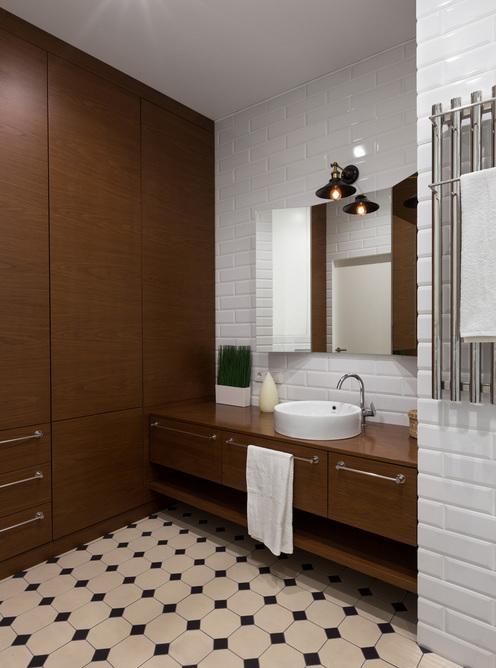 Ретро плитка, брутальная полотенцесушилка и характерный плафон над зеркалом привносят атмосферу лофта в ванную комнату.