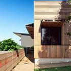 Перфорация присутствует как на ставнях, так и на фасаде пристройки с детскими комнатами.