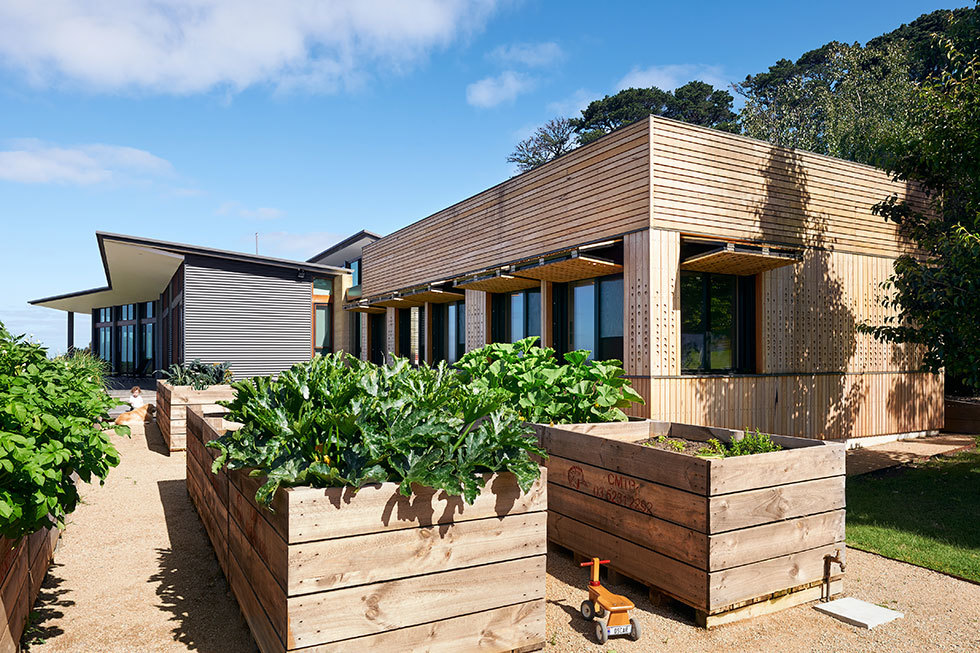 У пристройки с детскими комнатами удачно разместились поднятые грядки огорода. Дерево грядок хорошо сочетается с деревянным фасадом пристройки.