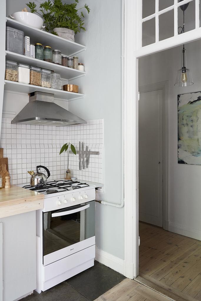 Мелкий белый кафель и вытяжка из нержавейки часто встречаются в интерьерах стиля лофт.