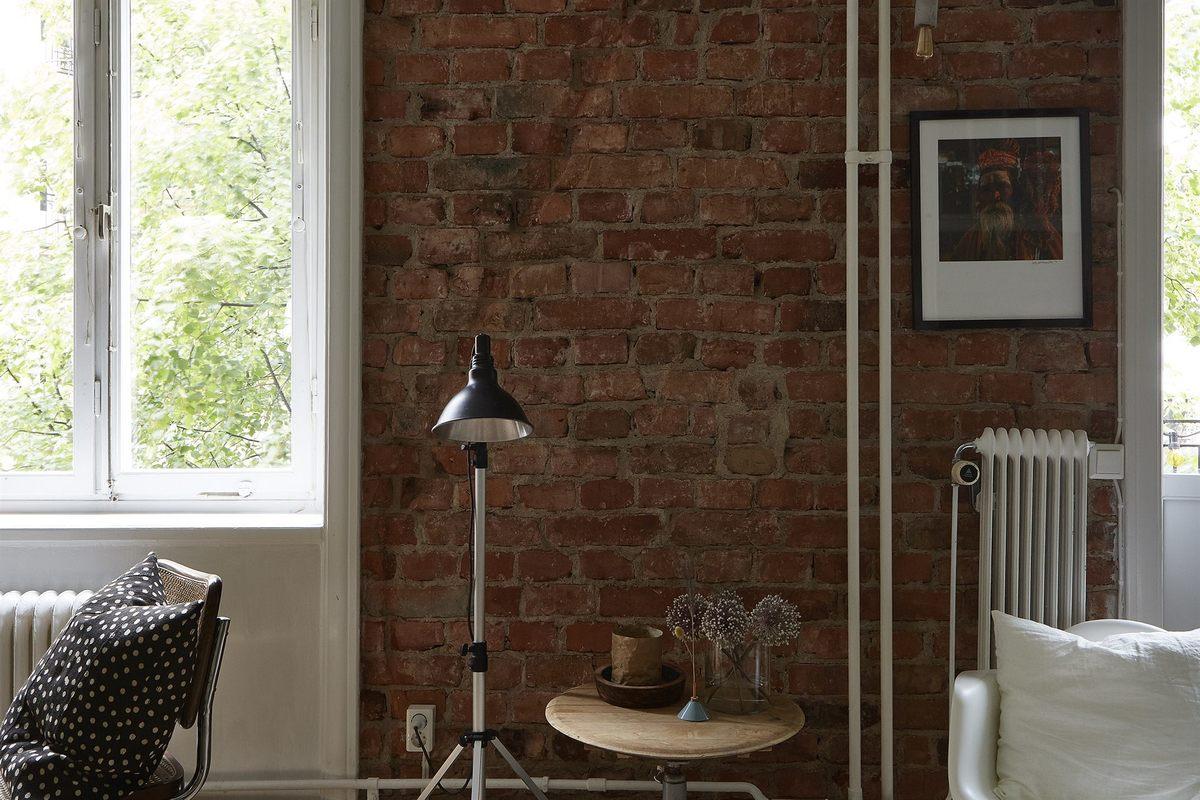 Неоштукатуренная кирпичная стена и открытые трубы придают квартире ощущения лофта, которое подкрепляется удачно подобранными светильниками и столиком.