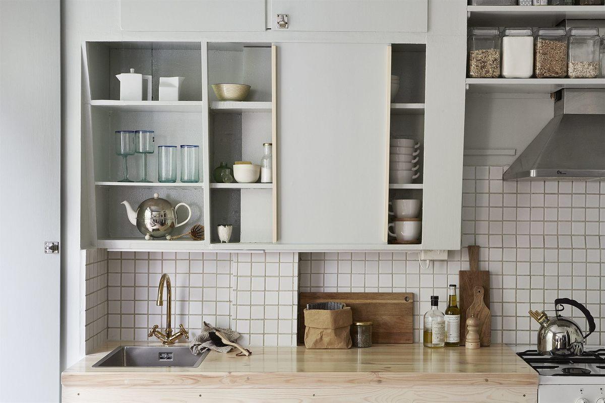 Простую и незамысловатую кухонную мебель очень оживляет столешница из светлого дерева.