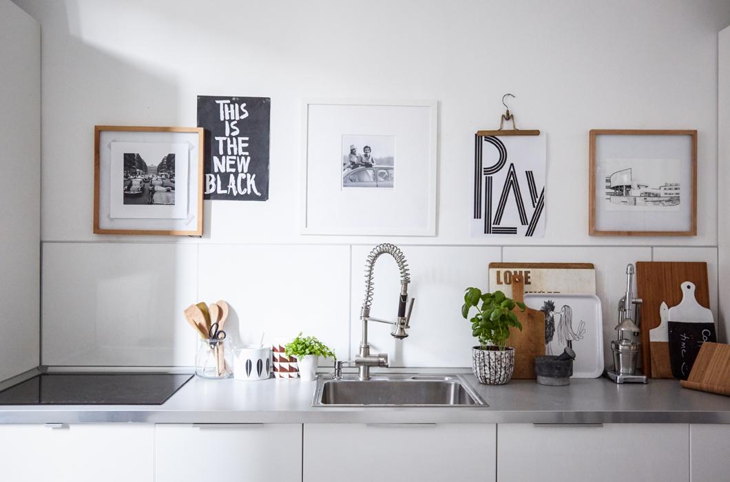 Минималистичный дизайн кухни дополнен арт объектами над кухонным фартуком. Кухонный фартук однотонно белый, столешница из нержавейки.