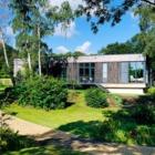 Фасад дома обшитый мореным каштаном идеально вписался в лесной пейзаж.