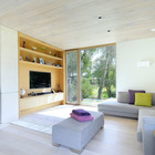 В светлой гостиной использована встроенная мебель, а за углом находится кухня.