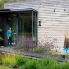 Входом в дом служат больший остекленные двери. (маленький дом,архитектура,дизайн,экстерьер,интерьер,дизайн интерьера,мебель,современный,вход,прихожая)