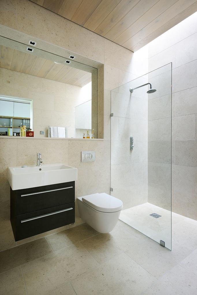 Мансардное окно в потолке над душем днем освещает ванну. Утопленное в стену зеркало позволило сделать полку для туалетных принадлежностей.