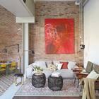 Кирпичная стена служит вполне уместным обрамлением яркой картине на стене.