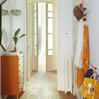 Несмотря на то что коридор не имеет своих окон, он кажется светлым благодаря светлой отделке и ярким разноцветным крючкам для одежды.