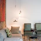 Причудливо развешенные светильники должны, по задумке дизайнера, создавать интересную игру света в гостиной.