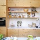 В противовес белой мебели под кухонной столешницей у окна, кухонная мебель из массива дерева с противоположной стороны просто вскрыта лаком. Это оживляет небольшую светлую кухню.
