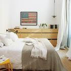 Второй комод в спальне расположен вдоль всей стены рядом с кроватью. Он изготовлен из того же дерева что и мебель на кухне. И хотя кухня далеко, это стилистически объединяет эти помещения.