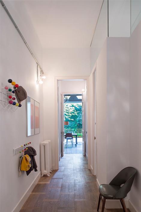 Через коридор дом просматривается насквозь и видна зелень дворика за домом. Верхняя часть стены ванных комнат остеклена, благодаря этому в прихожую проникает свет.