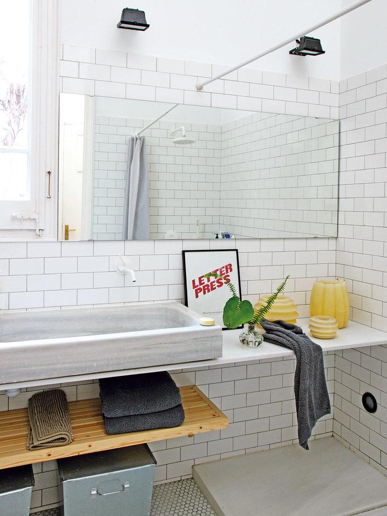 Дизайн ванной традиционно, для стиля лофт, сдержанный и простой с большим умывальником. При этом ванна очень светлая благодаря окну и белому кафелю на стенах.